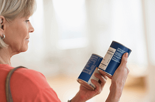 Checking food labels to see if they comply with a heart healthy diet